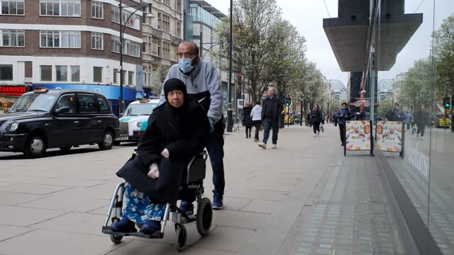 a member of the public wears a face mask as he pushes a relative in a wheelchair during the coronavirus pandemic on oxford street on march 18 2020 in... - brian dayle coronavirus stock videos & royalty-free footage