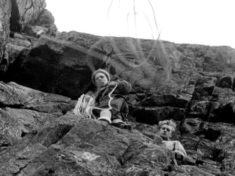 a member of the raf mountain rescue team throws a rope down from a rockface - felswand stock-videos und b-roll-filmmaterial