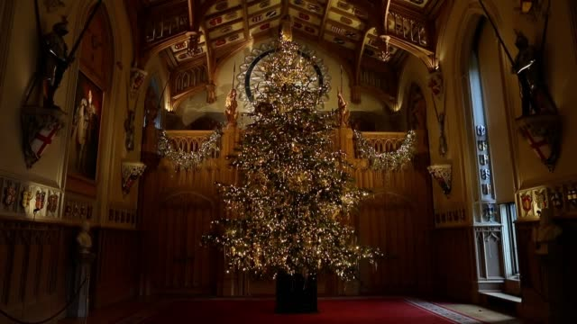 A member of the Royal Collection Trust staff puts the finishing touches to a twenty foot Nordmann fir tree which stands at the end of the St George's...
