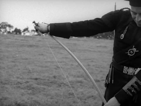 A member of the Royal Company of Archers checks his bow at the start of a competition to win a silver arrow
