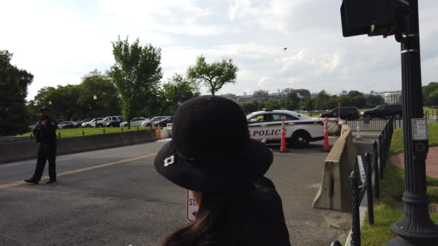 stockvideo's en b-roll-footage met a member of the secret service yells at tourists crossing against a signal to hurry up near the white house at the ellipse after a man set himself on... - ellips