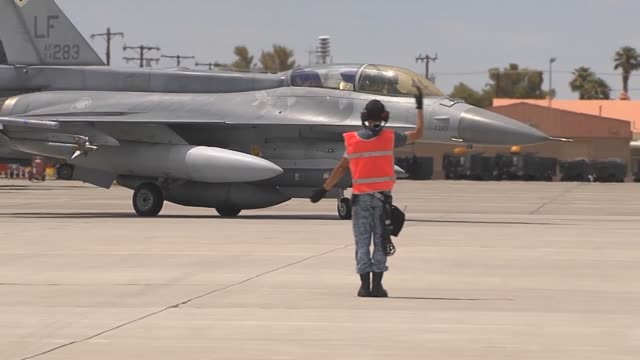vídeos de stock, filmes e b-roll de a member of the singaporean air force ground crew marshals an f16 in for final checks prior to flight during red flag 143 jul 16 2014 at nellis air... - nellis air force base