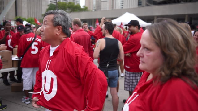 a member of unifor put on a red tshirt with the union logo in the front the toronto labor day parade is a traditional annual event in the canadian... - fackförbund bildbanksvideor och videomaterial från bakom kulisserna