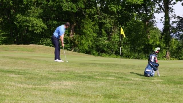 a member putting for the first green at bryn meadows golf club as restrictions on playing golf in wales have been eased but still differ to golf in... - green golf course stock videos & royalty-free footage