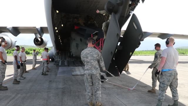 Members of 101st Combat Aviation Brigade Fort Campbell Kentucky as well as other supporting units load Blackhawk helicopters onto a C17 Globemaster...