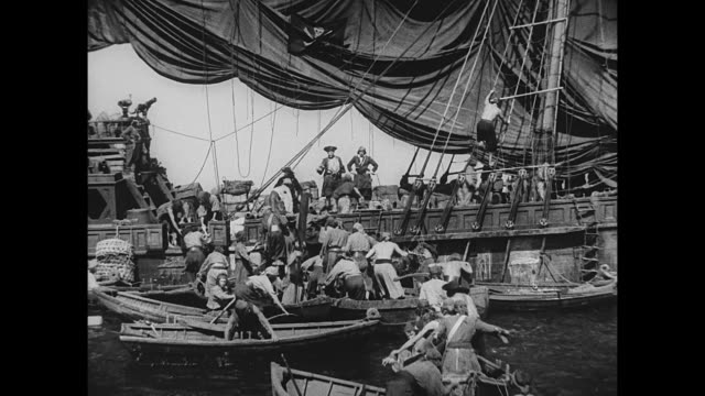 members of a crew climb onto a large pirate ship - seeräuber stock-videos und b-roll-filmmaterial