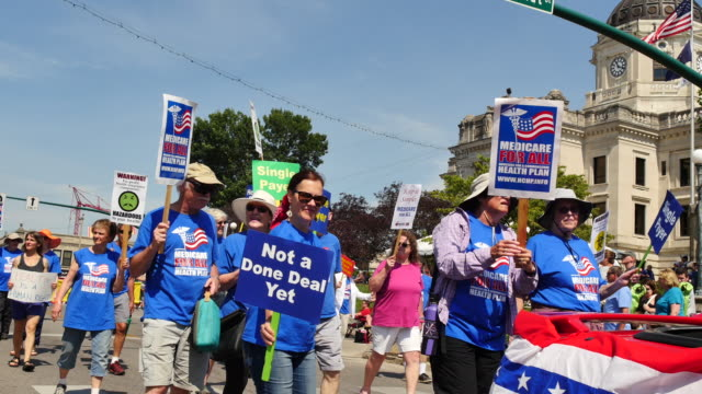 members of a group in favor of medicaid for all march in the bloomington indiana 4th of july parade in 2017 many in the parade were carrying signs... - medicaid stock videos and b-roll footage