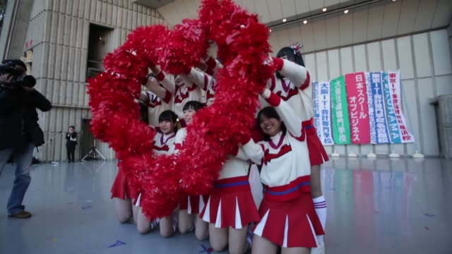 members of a japanese vocational school cheerleading team perform on stage waving pom poms to form the word 'love' students at a job hunting rally in... - チアリーダー点の映像素材/bロール