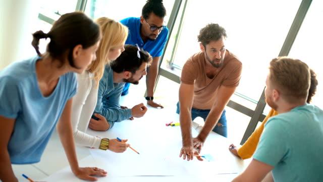 vidéos et rushes de membres d'une société de conception de démarrage lors d'une réunion. - agence de design