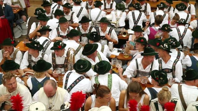 vidéos et rushes de members of a traditional bavarian marching band drink beer in the armbrustschuetzenzelt tent following the oktoberfest parade of costumes of folk and... - culture allemande