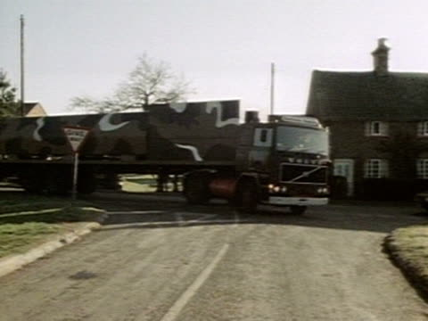 members of cnd drive a replica cruise missile launcher through a village in east anglia in protest at cruise missiles being based at greenham common... - nuklearbombe stock-videos und b-roll-filmmaterial