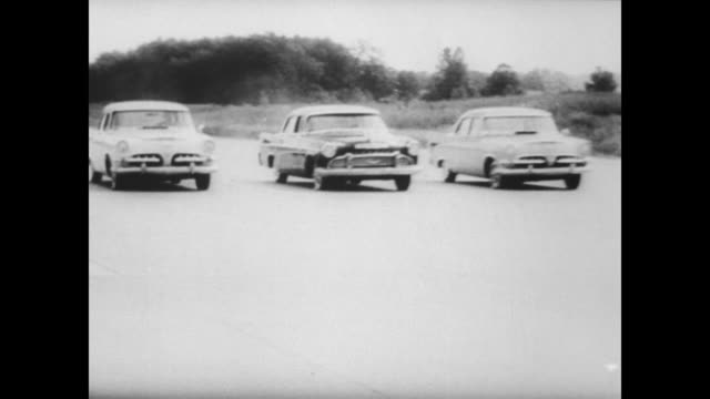 members of congress watch a display of car safety in chelsea michigan / car pulls into the automobile proving grounds stopping at the guard house /... - 横滑り点の映像素材/bロール