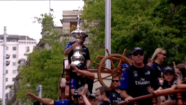 Members of Emirates Team New Zealand in boatshaped float with America's Cup at annual Farmers Santa Parade along Queen Street in Auckland