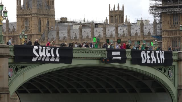 members of extinction rebellion hang a banner across westminster bridge campaigning against multinational oil giant shell highlighting the climate... - focus concept stock videos & royalty-free footage