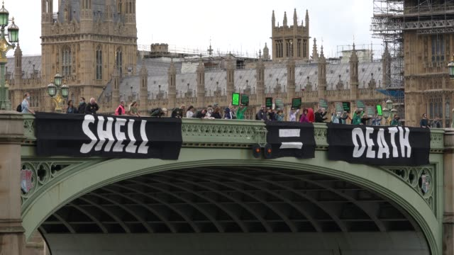 members of extinction rebellion hang a banner across westminster bridge campaigning against multinational oil giant shell highlighting the climate... - global business stock videos & royalty-free footage
