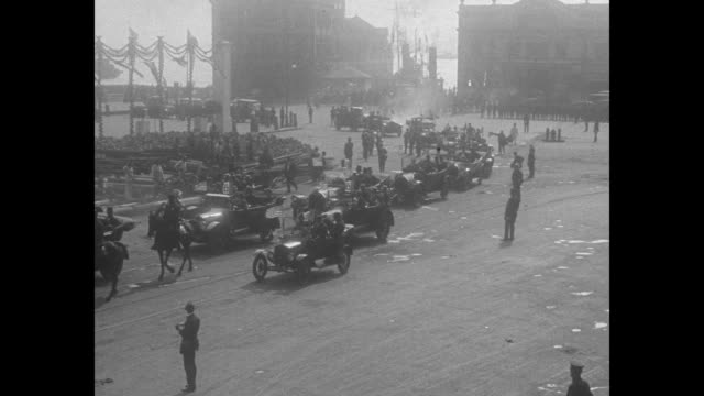 members of italian war mission riding in cars in motorcade down street / overhead shot of motorcade riding down street with crowd on either side /... - parade stock videos & royalty-free footage