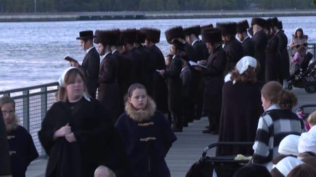 members of new york city's hasidic community mark rosh hashana, the jewish new year, by performing tachlich - a custom to cast away sins - by the... - rosh hashanah stock videos & royalty-free footage