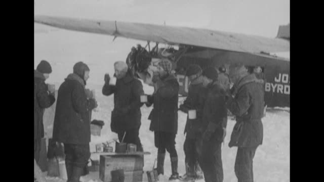 members of richard e byrd's arctic expedition drink from mugs eat outdoors on icy shore as the plane josephine ford stands behind / byrd wearing fur... - mitten stock videos and b-roll footage