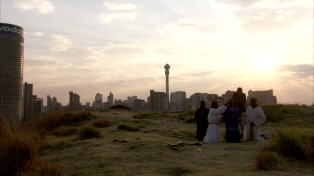 Members of the 12th Apostolic Church pray on a hill overlooking a city. Available in HD.