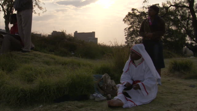 Members of the 12th apostolic church pray on a hill.