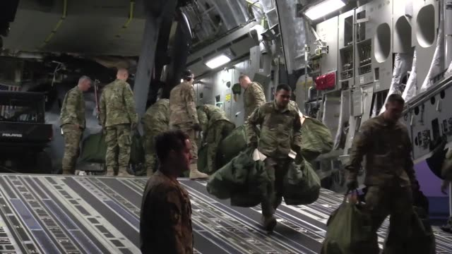 vídeos de stock e filmes b-roll de members of the 33rd expeditionary rescue squadron offload supplies and an hh60g pave hawk helicopter from a c17 globemaster iii at kandahar airfield... - kandahar