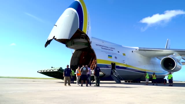Members of the 36th Mobility Response Squadron assigned to Andersen Air Force Base Guam unload building materials from a Russian Antonov AN124 cargo...
