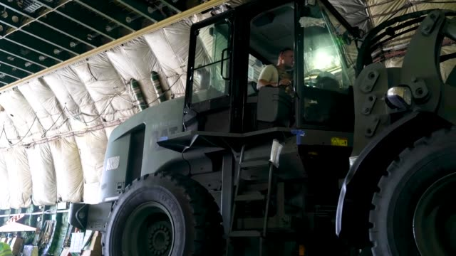 members of the 36th mobility response squadron assigned to andersen air force base, guam, unload building materials from a russian antonov an-124... - グアム点の映像素材/bロール