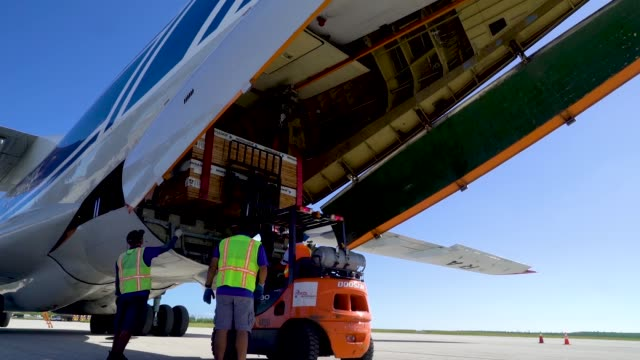 members of the 36th mobility response squadron assigned to andersen air force base, guam, unload building materials from a russian ilyushin il-76td... - グアム点の映像素材/bロール