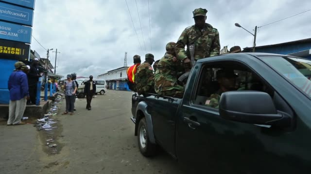 vídeos de stock, filmes e b-roll de members of the armed forces of liberia drive up to the main entrance to west point which was quarantined last night. an isolation unit was being... - febre hemorrágica