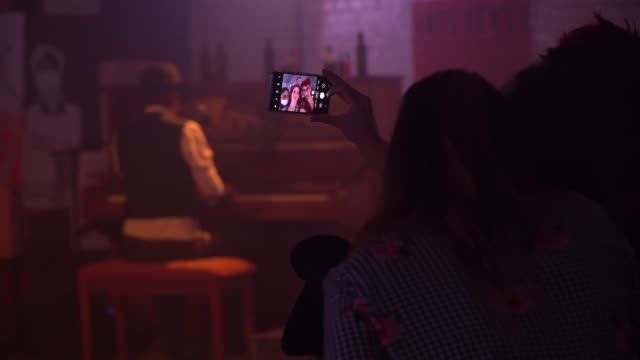 "members of the audience take a selfie whilst watching a performance during the ""lockdown town"" launch night at one night records on october 7, 2020... - photography themes stock videos & royalty-free footage"