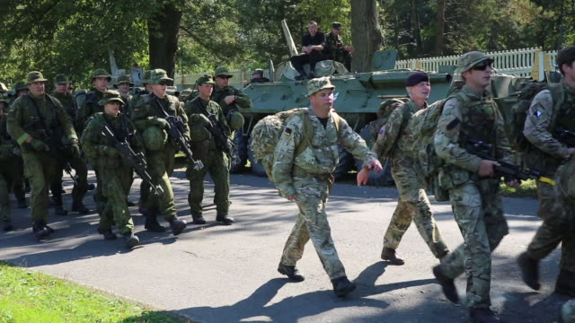 stockvideo's en b-roll-footage met members of the british army and the lithuanian army carrying rifles and packs march past armored personnel carriers while participating in the rapid... - britse leger