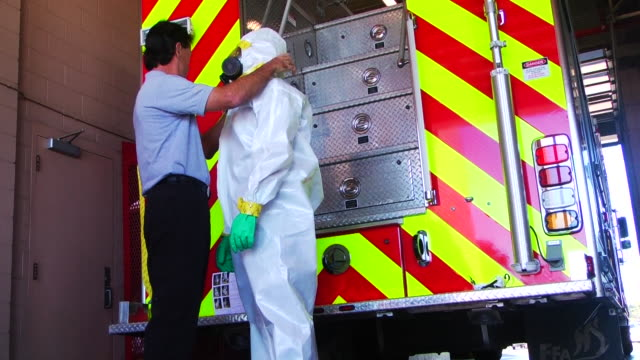 members of the caddo parish fire department try on special hazmat suits following the ebola crisis. - クリーンスーツ点の映像素材/bロール