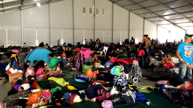 members of the central american migrant caravan rest under a tent in a stadium after arriving into the mexican capital yesterday on november 6 2018... - refugee stock videos & royalty-free footage