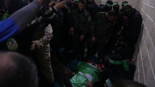 members of the ezzedine alqassam brigades the military wing of the palestinian islamist movement hamas carry the body of hamas official mazen faqha... - israel palestine conflict stock videos and b-roll footage