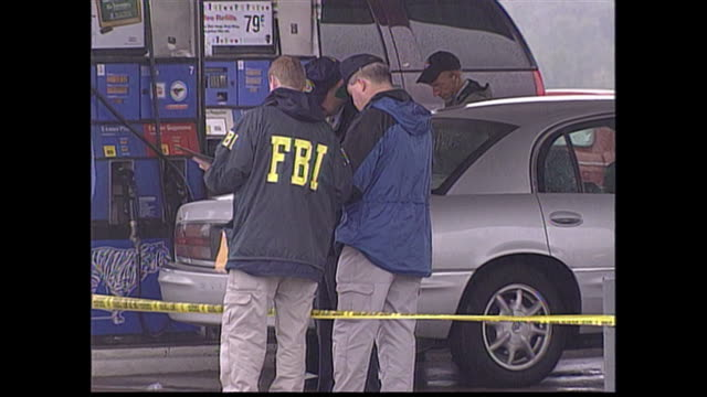 members of the fbi next to an open car, examining evidence where a dc sniper shooting took place. - 2002 stock videos & royalty-free footage