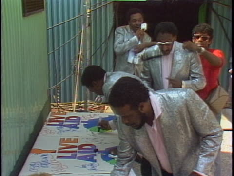 members of the four tops sign a poster for the live aid charity concert in the backstage area of the event. - music or celebrities or fashion or film industry or film premiere or youth culture or novelty item or vacations stock videos & royalty-free footage