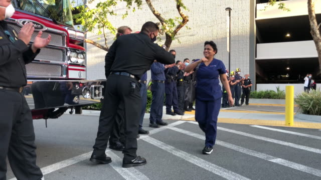 vidéos et rushes de members of the glendale police and fire departments pay tribute to healthcare workers during a shift change at glendale memorial hospital amidst the... - métier des services d'urgence