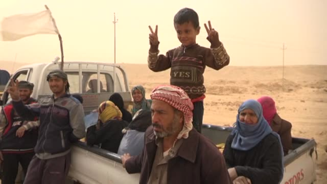 Members of the governmental forces assisted families fleeing combats in the Iraq's western desert bordering Syria as Iraqi forces fight against...