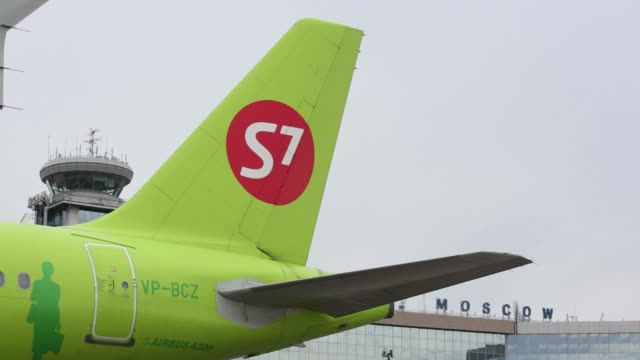 members of the ground crew refuel a passenger jet operated by s7 airlines at domodedovo airport in moscow russia on wednesday oct 26 an airbus... - 給油点の映像素材/bロール