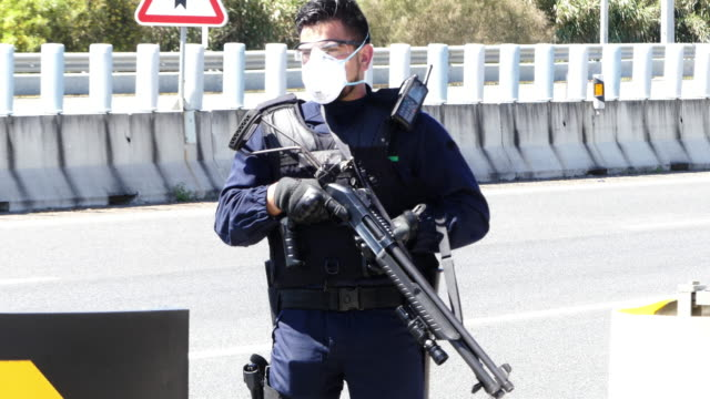 members of the guardia nacional republicana wearing protective gear control vehicles at a checkpoint set up off the a5 highway near cascais hospital... - カスカイス点の映像素材/bロール