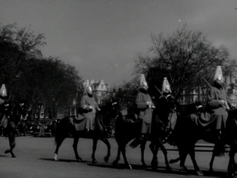stockvideo's en b-roll-footage met members of the household cavalry wear plumed helmets and winter capes as they ride their horses near hyde park 1953 - paardachtigen