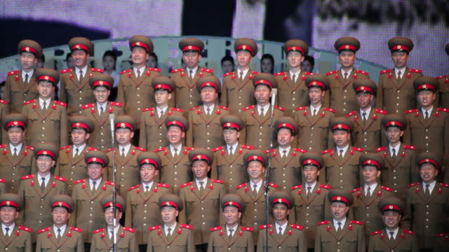 stockvideo's en b-roll-footage met members of the korean army sing in the pyongyang concert hall as a video plays behind them. - communisme