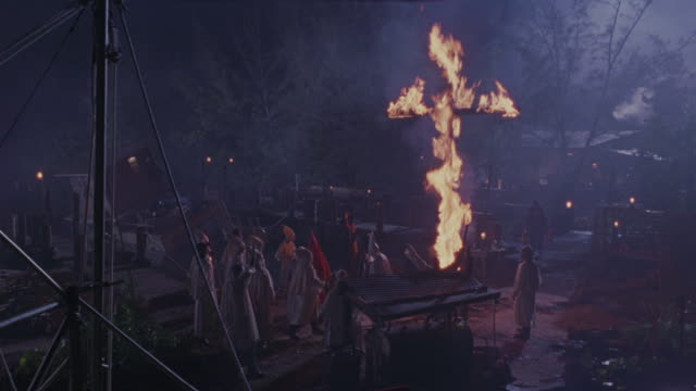 members of the ku klux klan congregate under a burning cross near a boat dock. - ku klux klan stock videos and b-roll footage