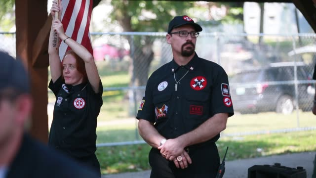 Members of the Ku Klux Klan watch a crowd of antiracism protesters during the KKK rally in Fireman's Park during a rally in Madison Indiana