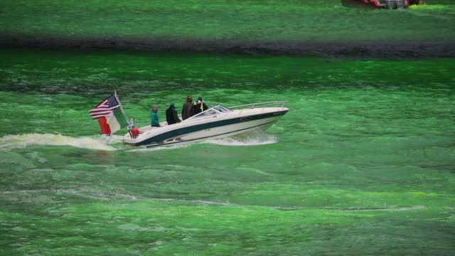 members of the local plumber's union use boats to mix dye in the chicago river to turn it green in celebration of st patrick's day on march 17 2018... - river green stock videos & royalty-free footage