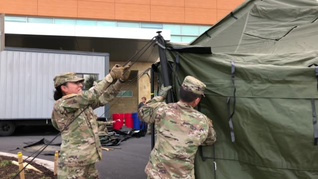 stockvideo's en b-roll-footage met members of the maryland army national guard work to set up a triage tent in the parking lot outside of the emergency room at adventist healthcare... - triage