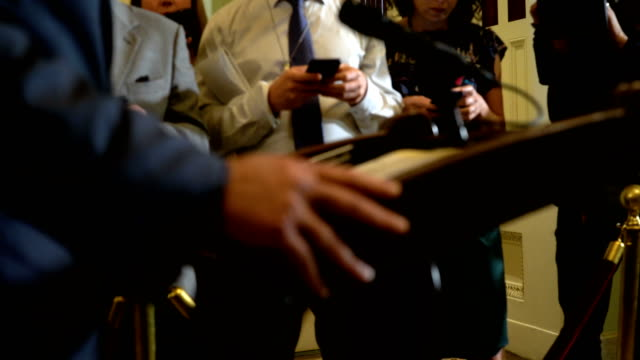 members of the media check on their phones as us senate minority leader sen chuck schumer approaches the podium for a news briefing after a weekly... - usa:s senat bildbanksvideor och videomaterial från bakom kulisserna
