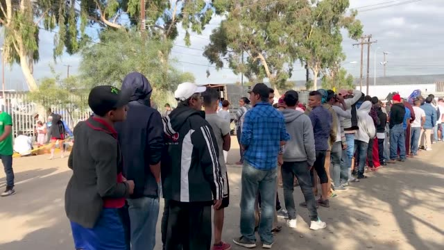 members of the 'migrant caravan' wait in line for food outside a temporary shelter set up for members of the caravan on november 26 2018 in tijuana... - tijuana stock videos & royalty-free footage