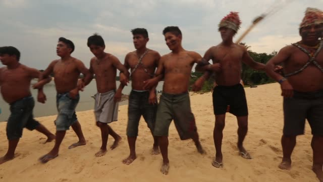 vídeos de stock, filmes e b-roll de members of the munduruku indigenous tribe dance along the tapajos river during a 'caravan of resistance'' protest by indigenous groups and supporters... - amazonas state brazil