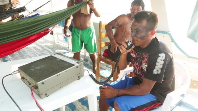 vídeos de stock, filmes e b-roll de members of the munduruku indigenous tribe gather and use a radio along the tapajos river during a 'caravan of resistance'' protest by indigenous... - amazonas state brazil